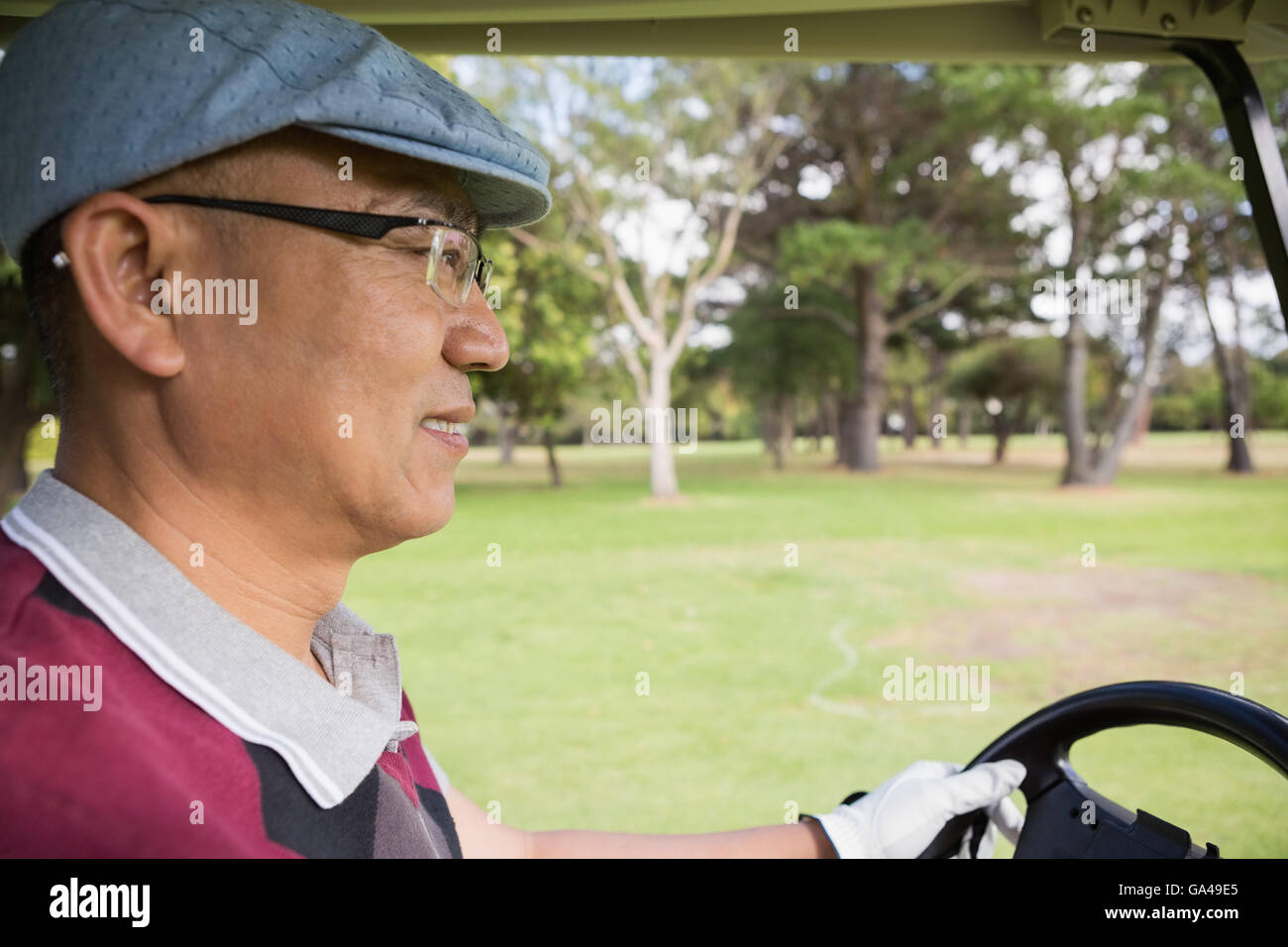 Golfer driving golf buggy - Stock Image