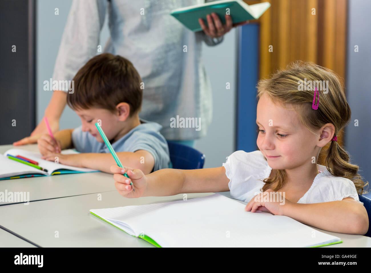 Schoolchildren writing on book against teacher - Stock Image