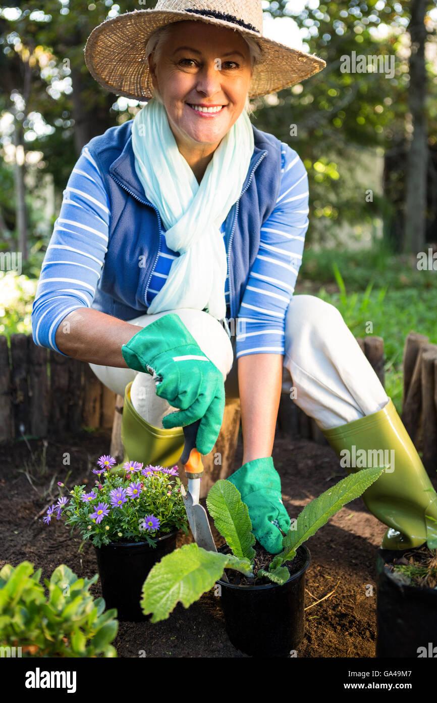 Portrait of happy gardener planting at garden Stock Photo