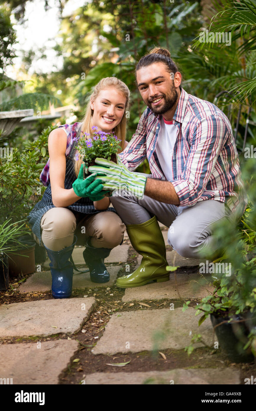 Portrait of gardeners holding potted plant at garden - Stock Image