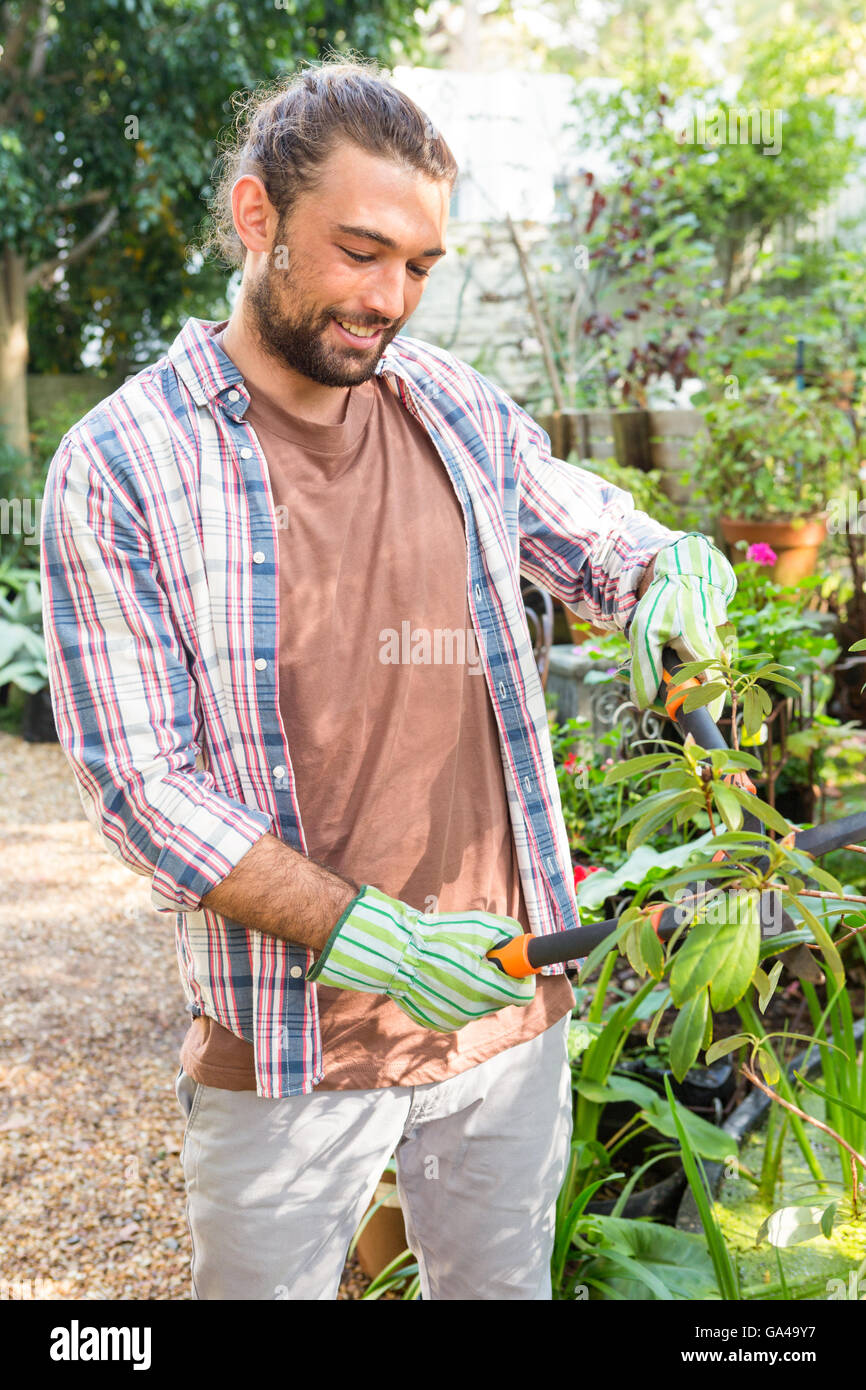 Happy hipster cutting twigs at from clippers at garden - Stock Image
