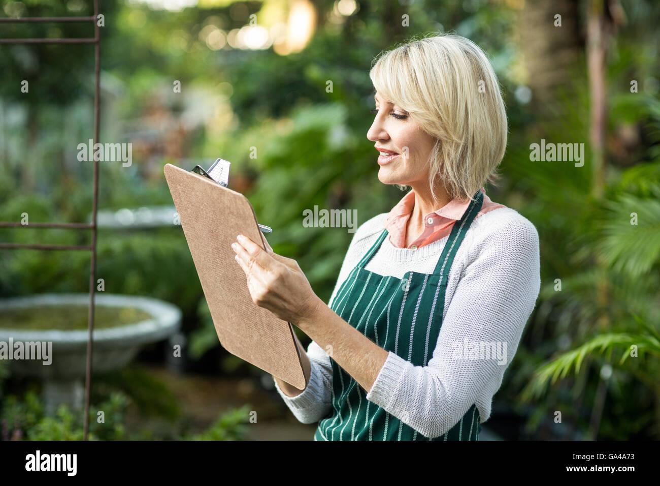 Female gardener writing in clipboard - Stock Image