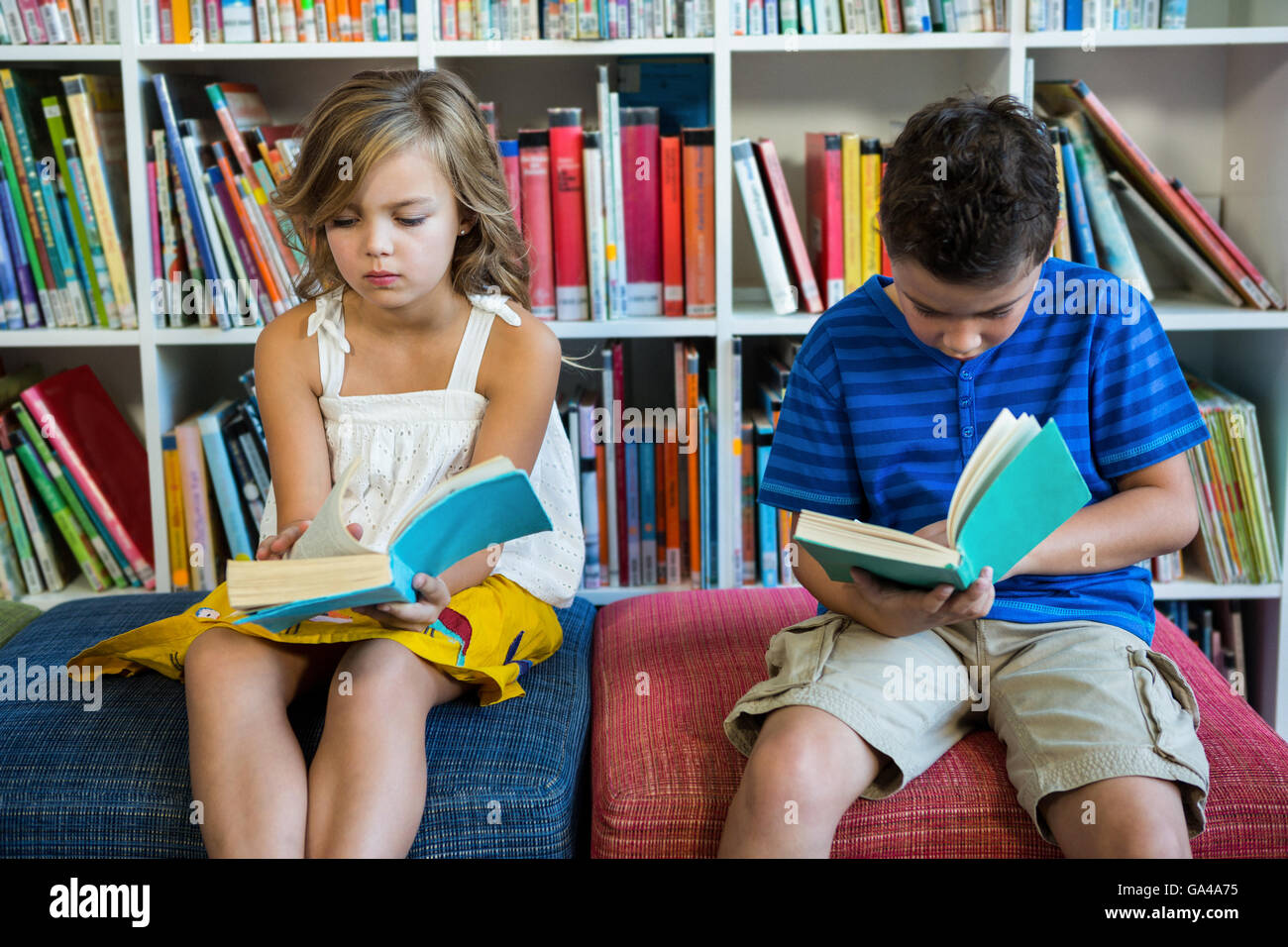 Elementary students reading books in school library - Stock Image