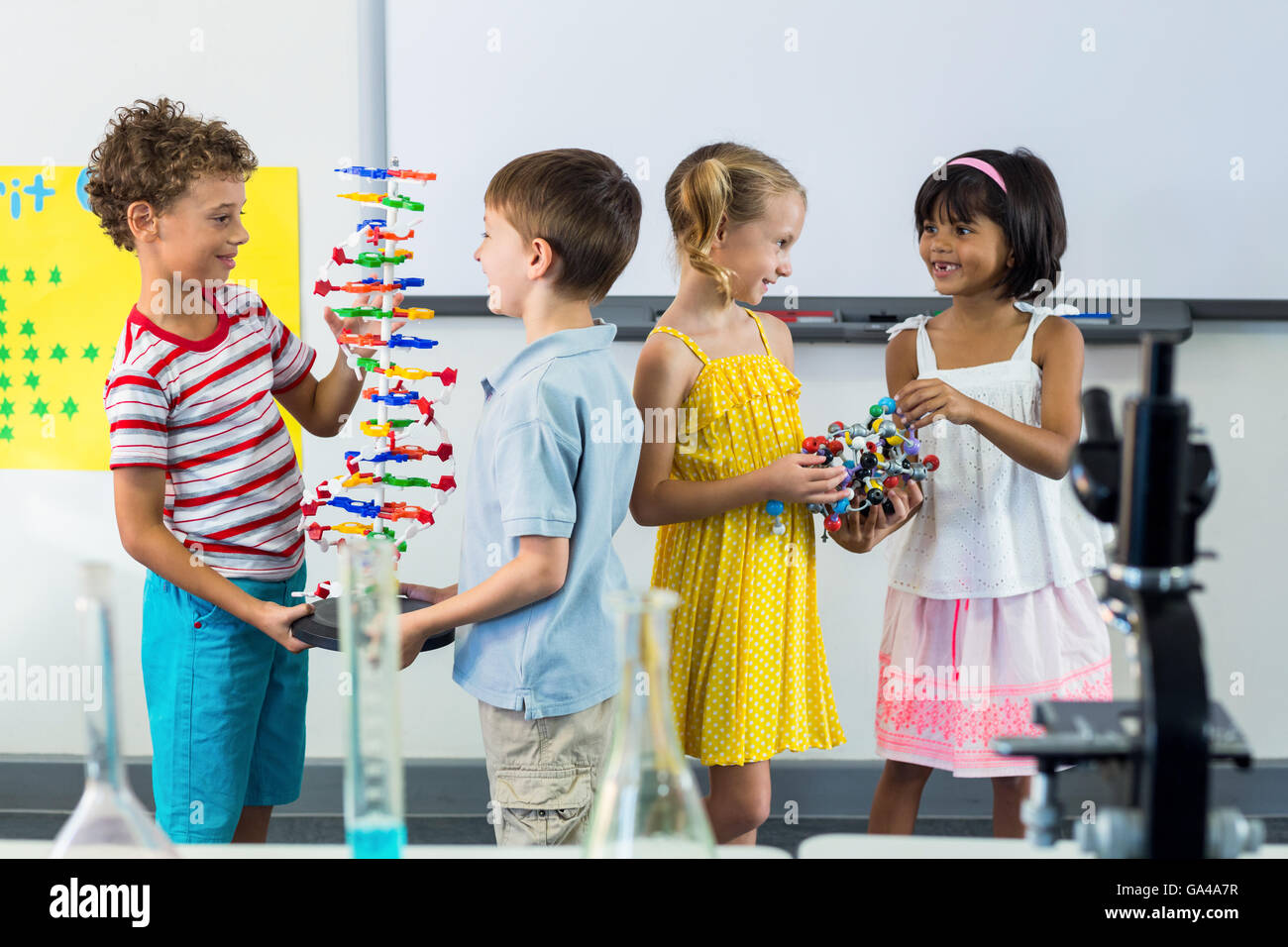 Happy schoolchildren in laboratory - Stock Image