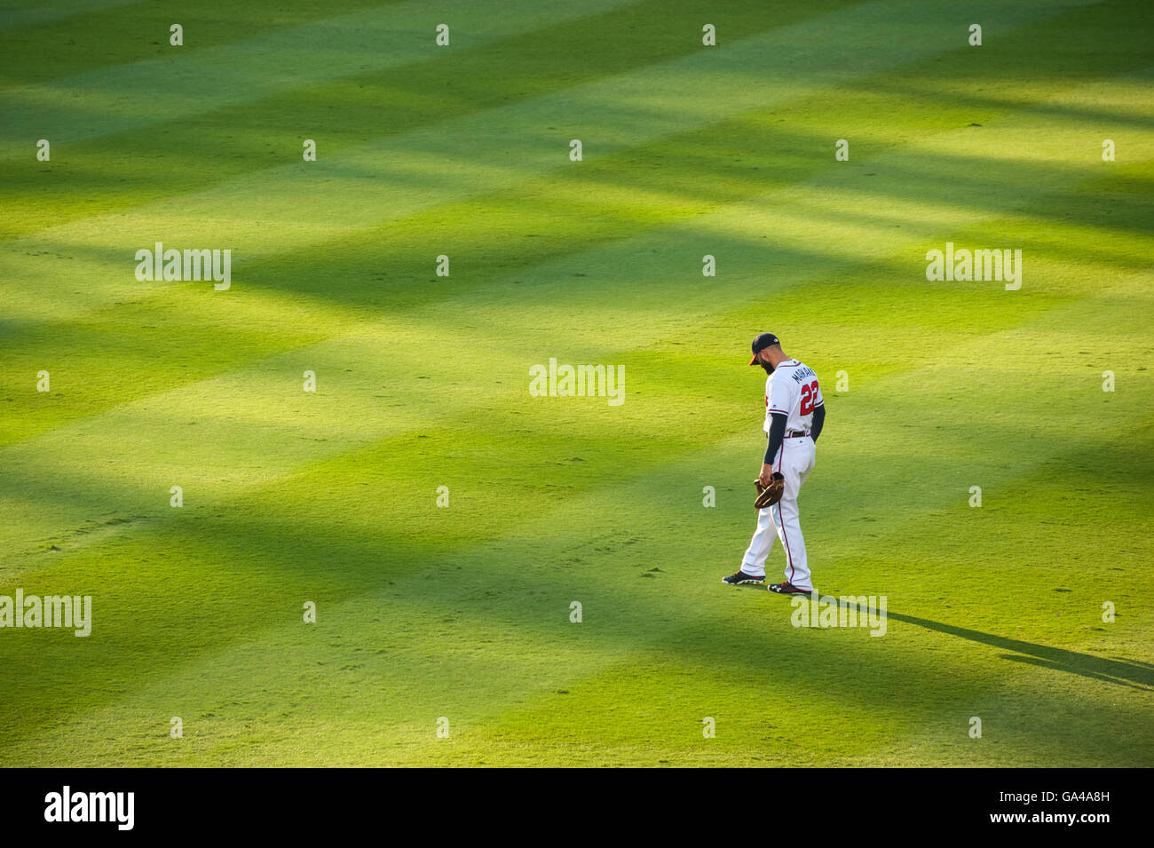 Atlanta Braves right-fielder, Nick Markakis, standing in the outfield as the sun sets on Atlanta, Georgia's - Stock Image