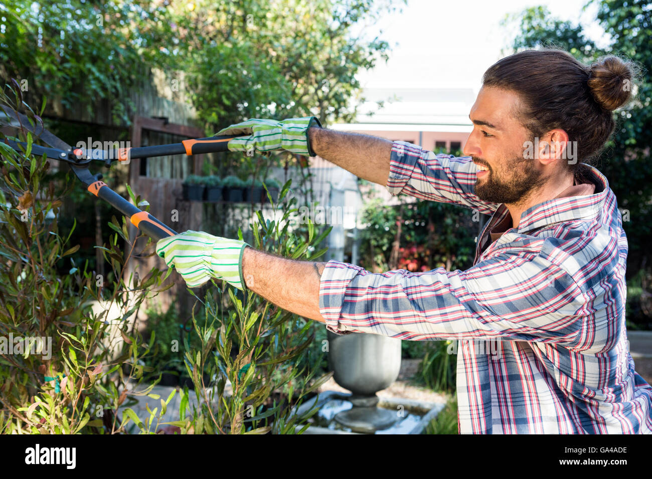 Happy hipster cutting hedges with clippers at garden - Stock Image