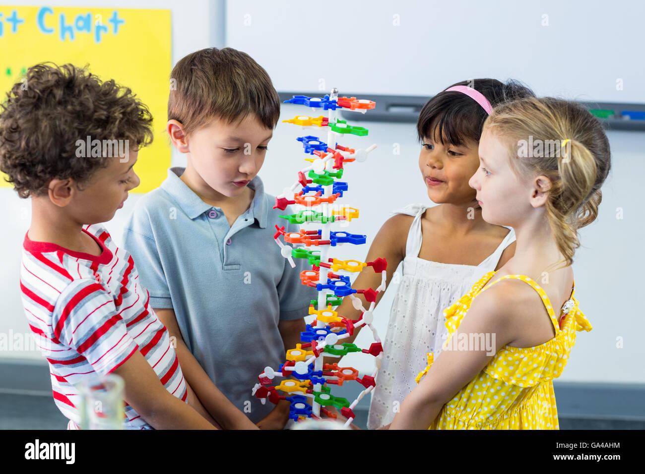Schoolchildren holding DNA model - Stock Image