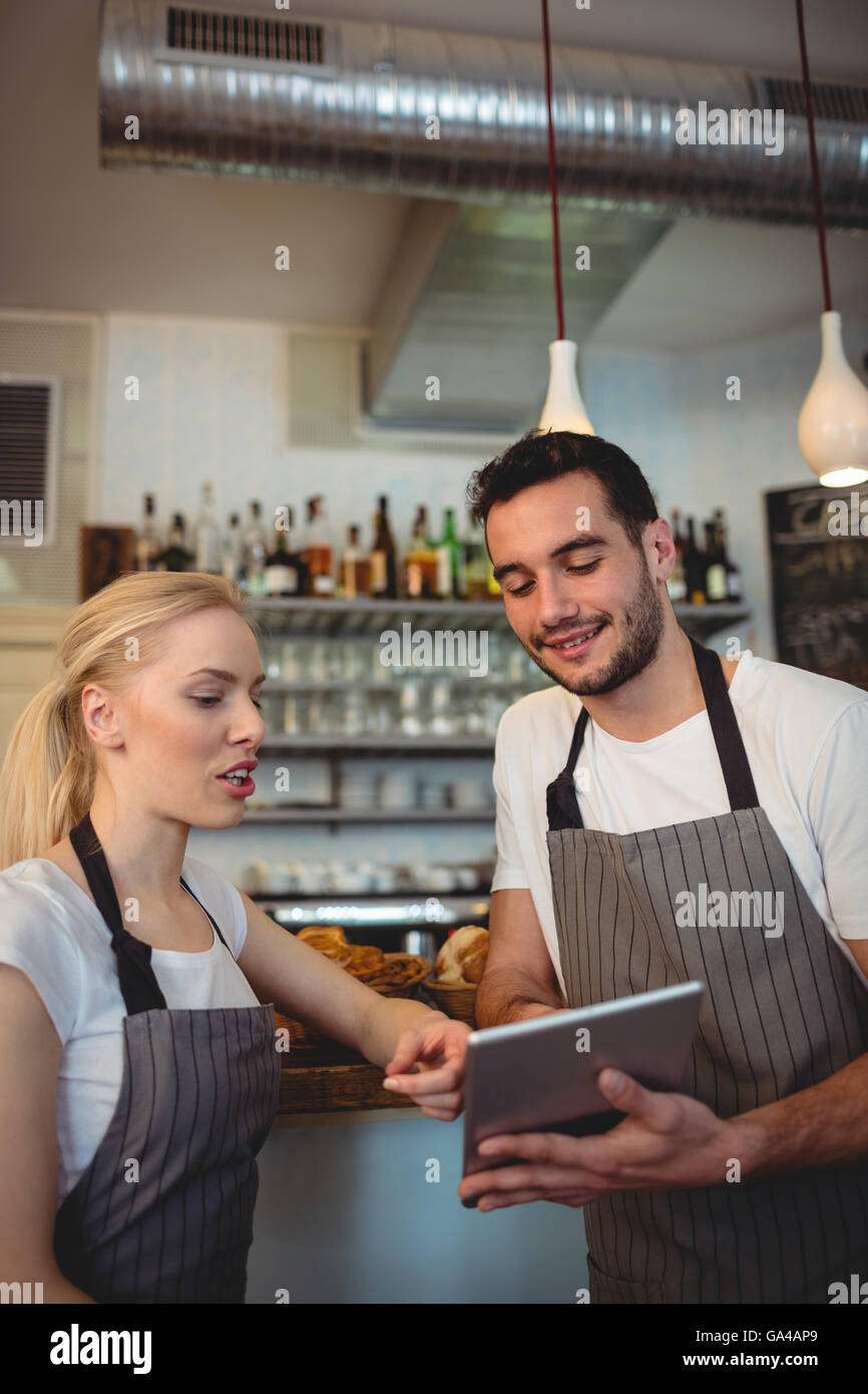Co-workers using digital tablet at cafe - Stock Image