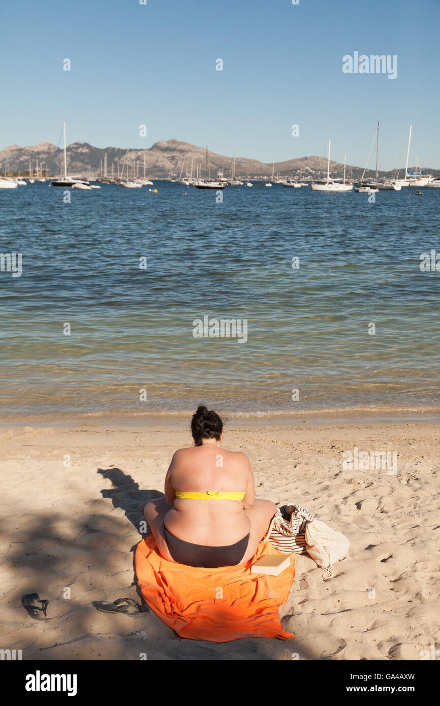 Obese woman on the beach seen from the rear back view, Majorca, Spain Europe - Stock Image