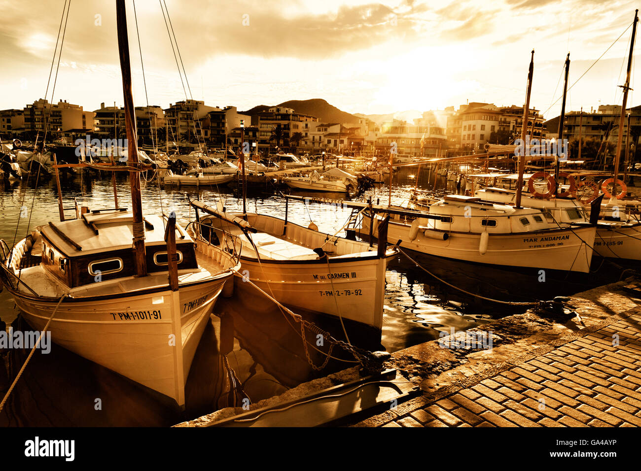 Sunset over boats in the harbour, Puerto Pollensa ( Pollenca ), Mallorca ( Majorca ), Balearic Islands, Europe - Stock Image