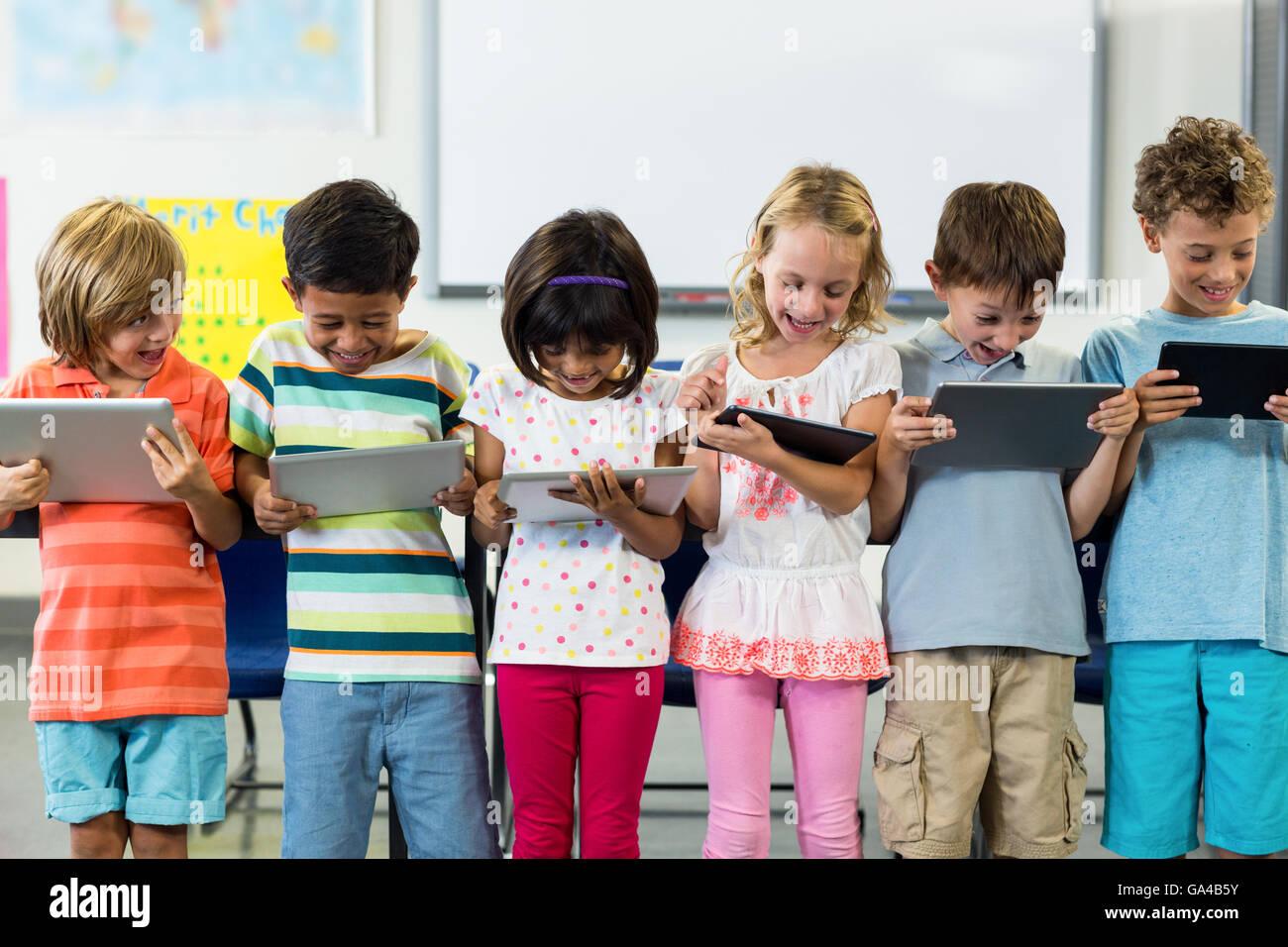 Smiling schoolchildren using digital tablet - Stock Image