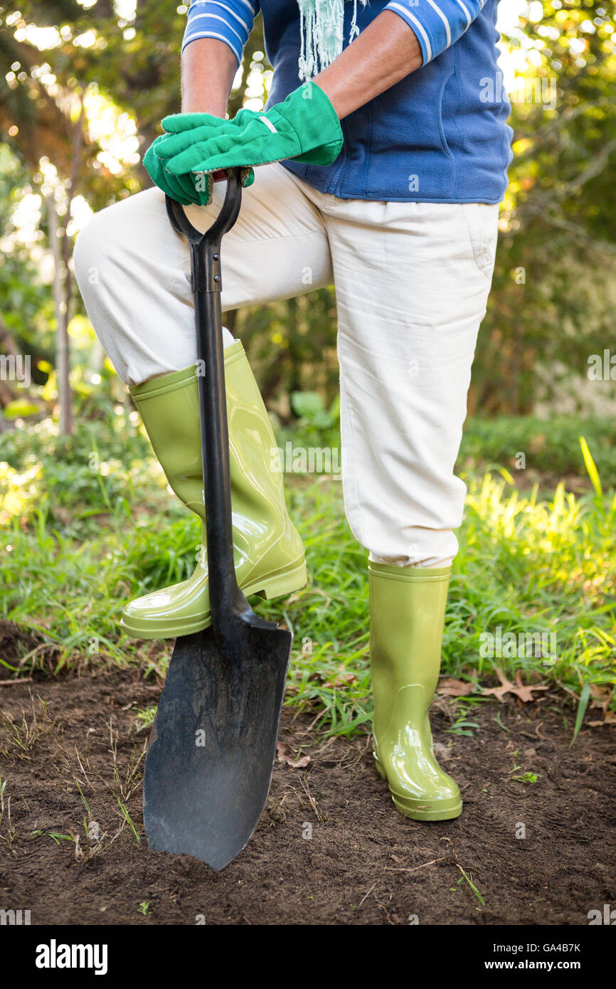 Low section of gardener standing with shovel at garden - Stock Image