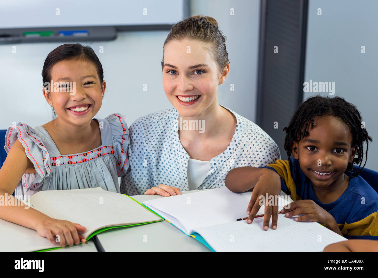Happy teacher with schoolchildren - Stock Image