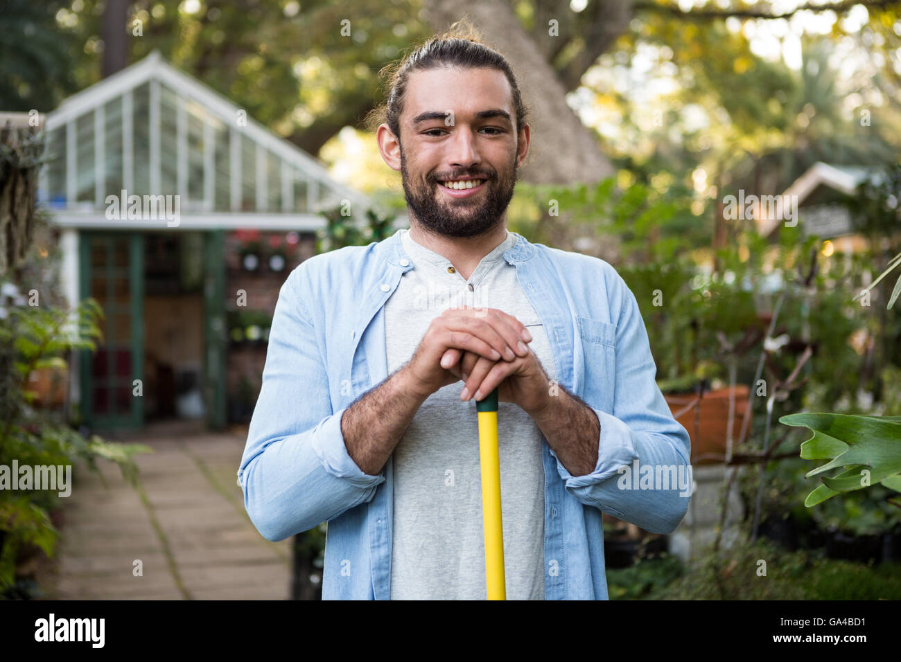 Portrait of happy gardener with work tool at garden - Stock Image