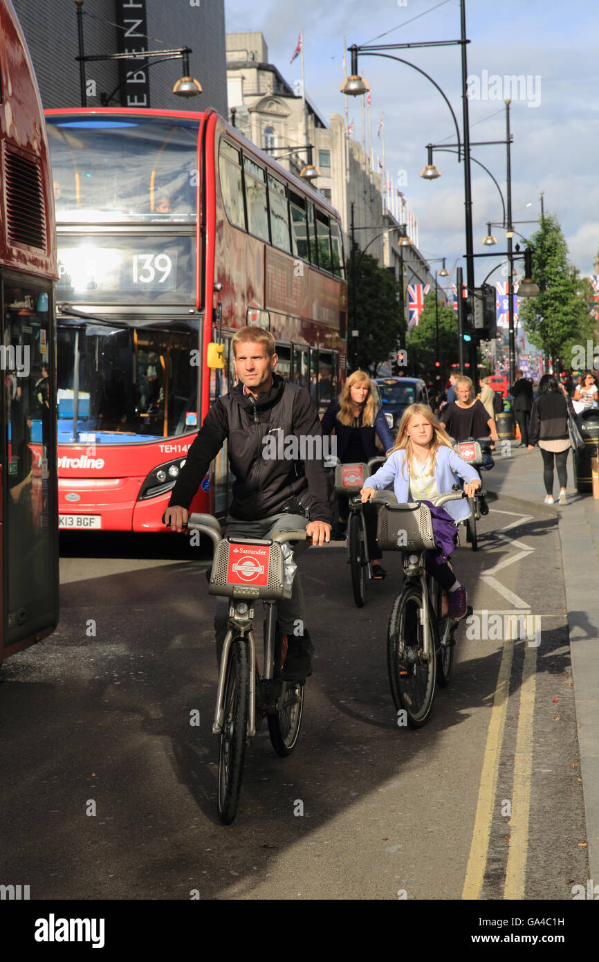 Tourist family struggling to cycle on Santander hire bikes, on London's busy Oxford Street, in the West End, in Stock Photo