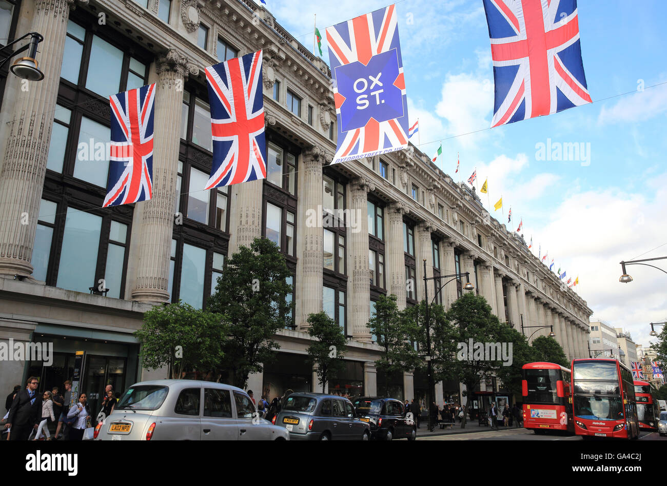 Union Jack flags line Oxford street by Selfridges department store, in central London, England, UK - Stock Image
