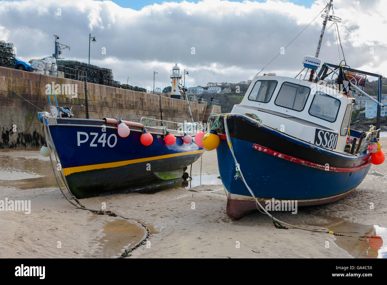Fishing boats aground at low tide, St Ives harbour, Cornwall, UK Stock Photo