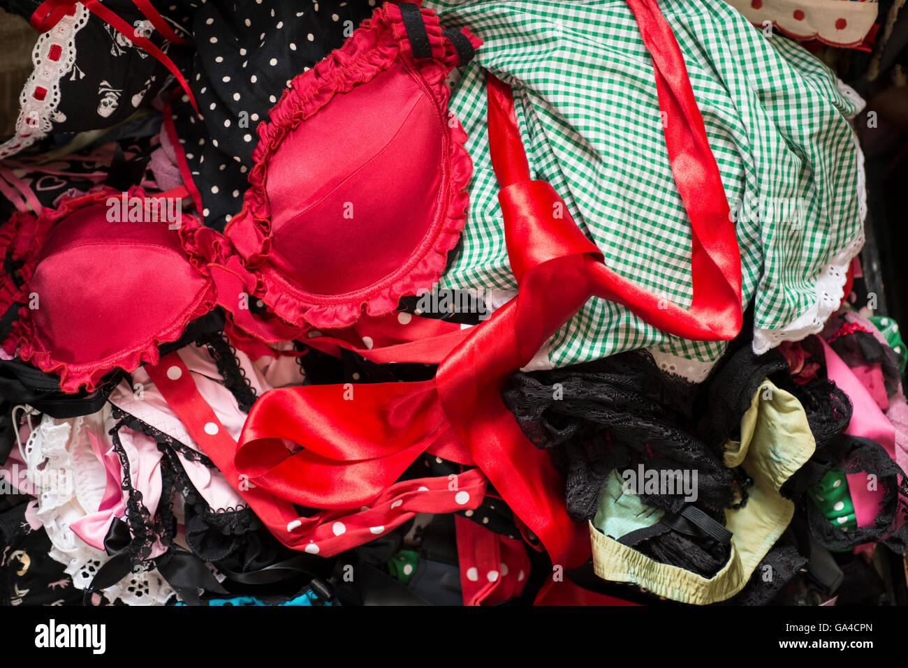A red brassiere on a heap of assorted garments. - Stock Image