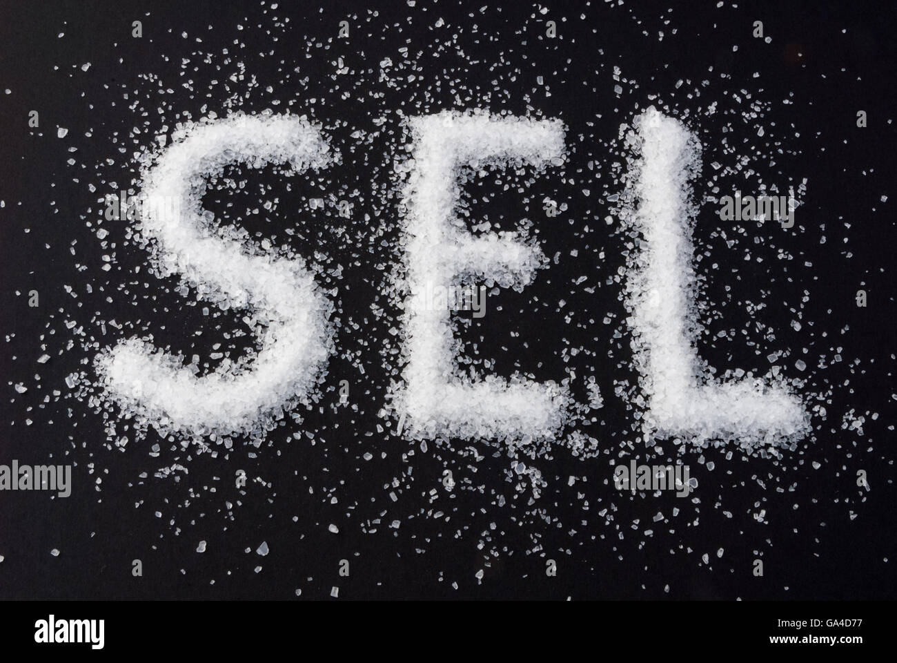 Coarse-grained sea salt with the French word SEL on black background - Stock Image