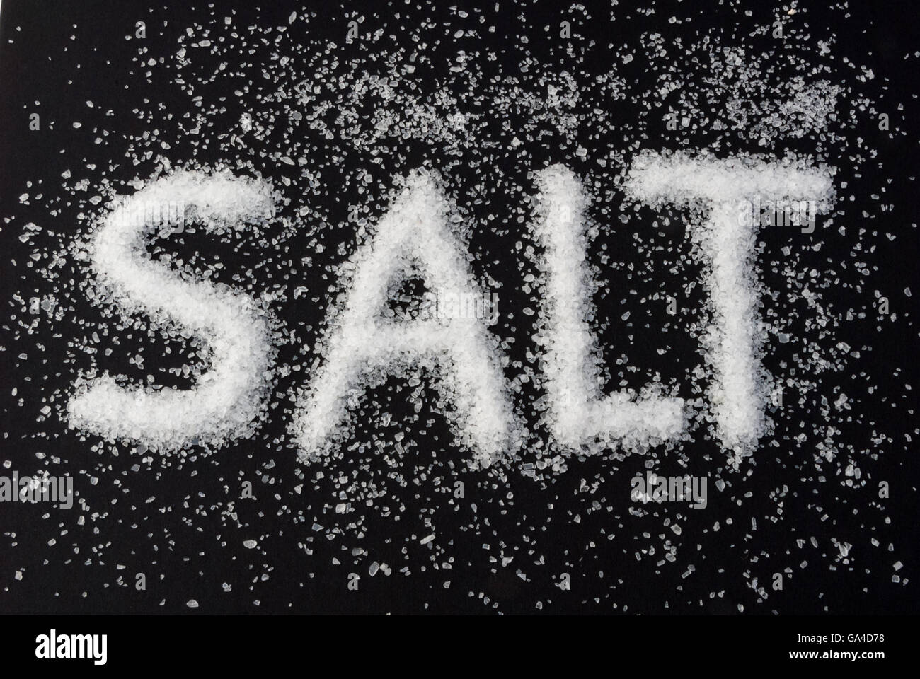 Coarse-grained sea salt with the word SALT on black background - Stock Image