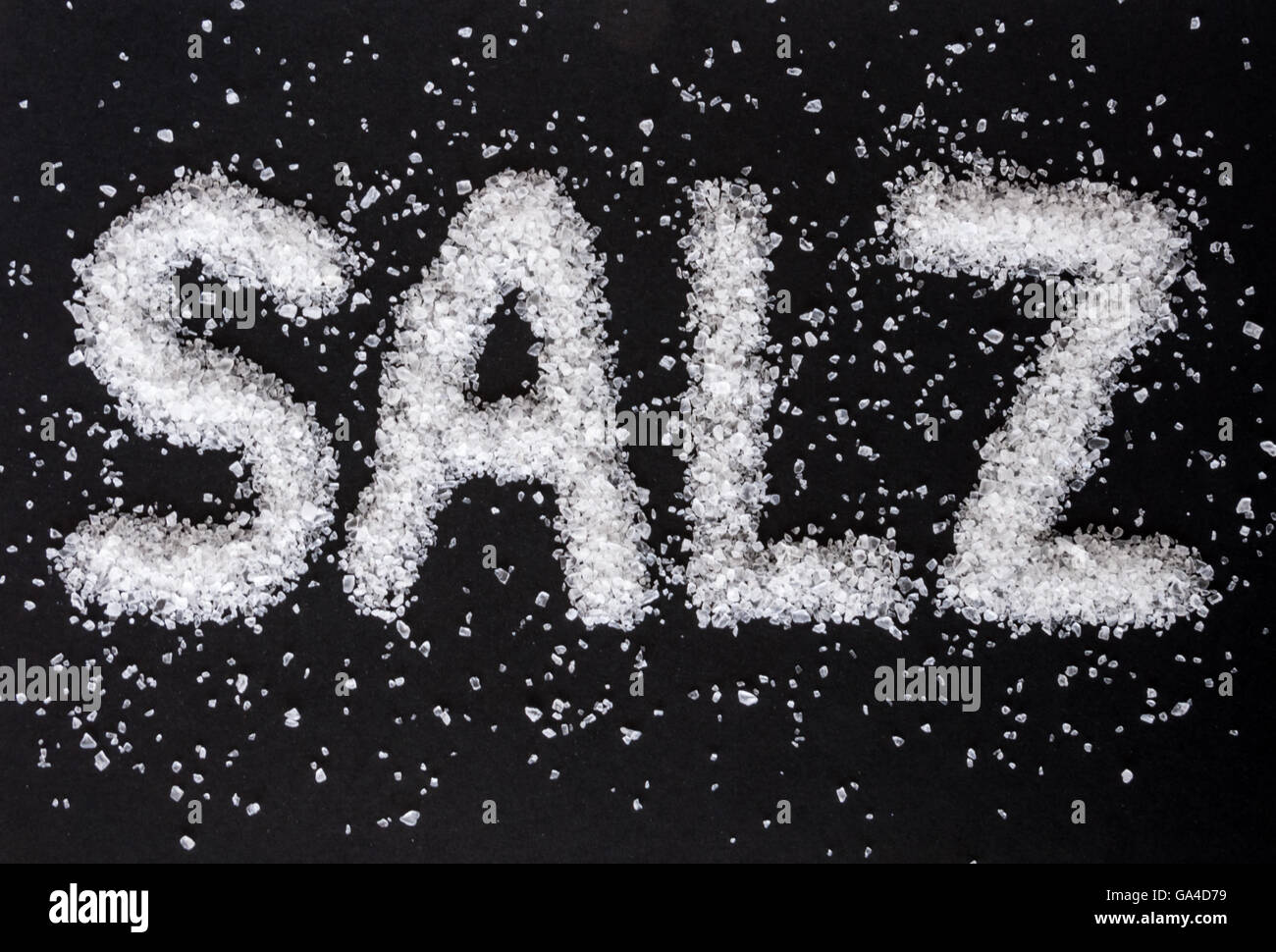 Coarse-grained sea salt with the German word SALZ on black background - Stock Image