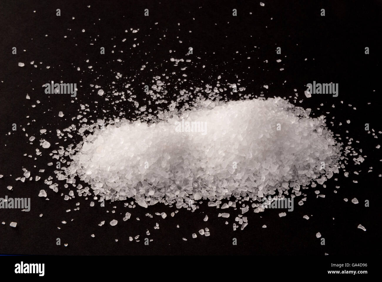Coarse-grained sea salt from the Atlantic on black background - Stock Image