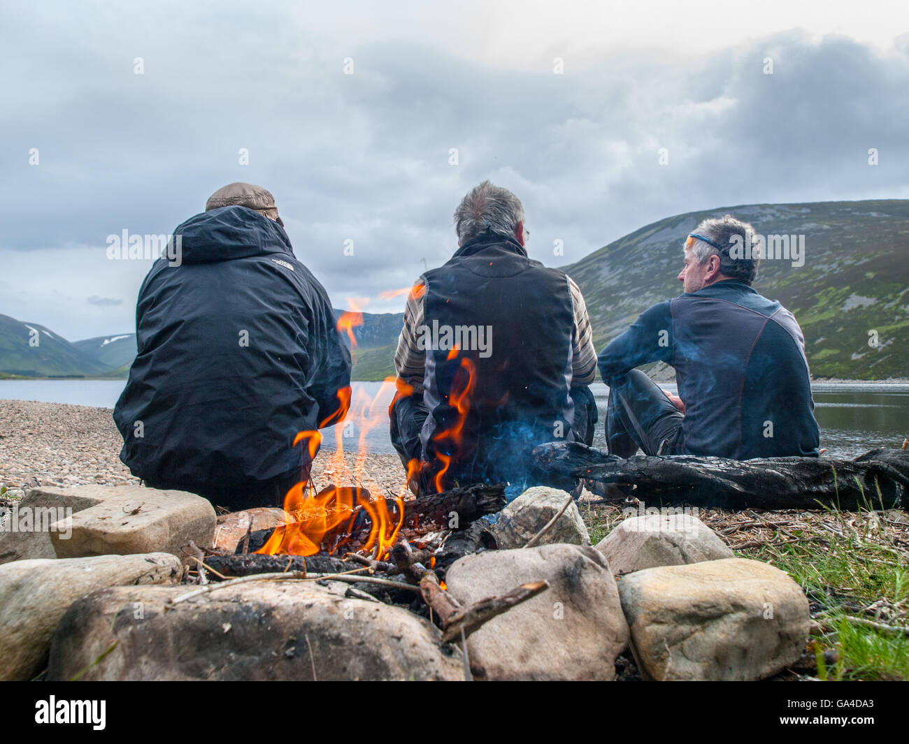Three men with their backs to a camp fire on a bike-packing trip in Scotland - Stock Image
