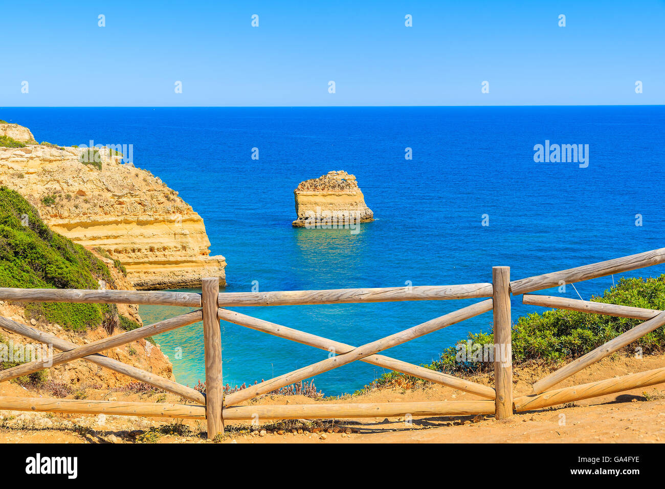 Wooden fence on cliff path on coast of Portugal in Algarve region near Praia de Marinha beach Stock Photo