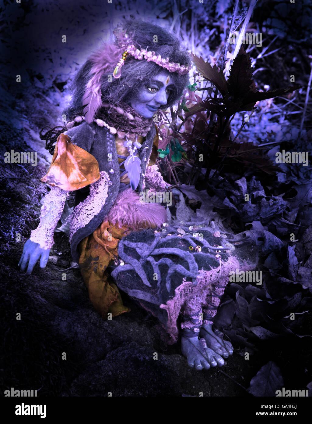 violett fairy doll figure sitting on stone in woodland - Stock Image