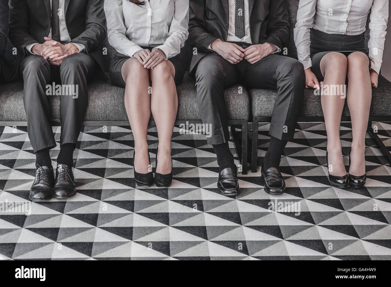 Business people waiting for job interview sitting in a row - Stock Image