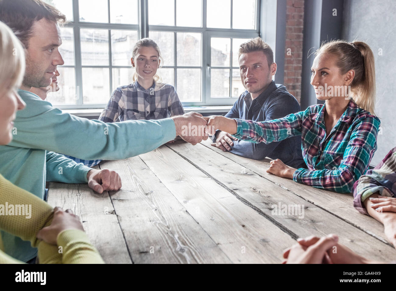 Modern business meeting concept, people on casual clothes sitting around wooden table - Stock Image