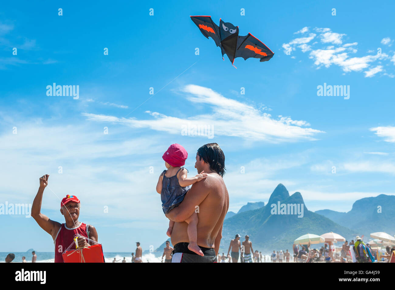 RIO DE JANEIRO - MARCH 10, 2013: A beach vendor selling kites displays his merchandise for a father and child on - Stock Image