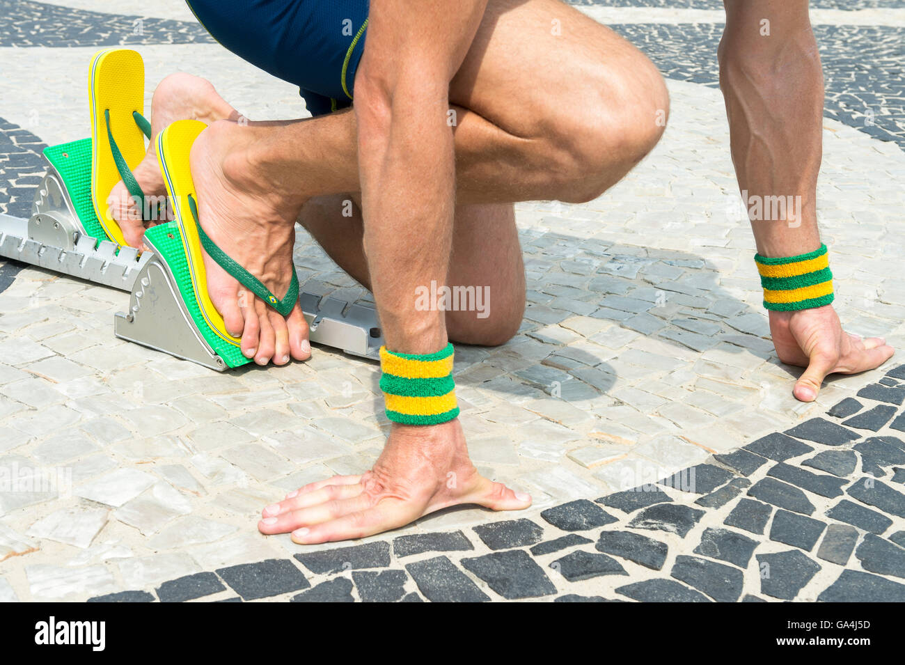 886c102455b92b Brazilian athlete wearing flip flops crouching at the start position in running  blocks on the tiles of the Copacabana boardwalk