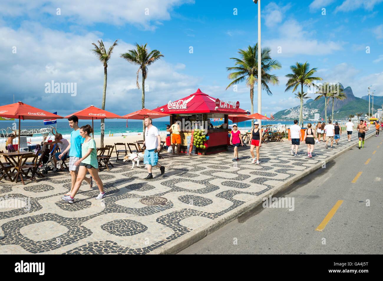 RIO DE JANEIRO - APRIL 3, 2016: Pedestrians pass Brazilians relaxing at a kiosk on a bright morning at Ipanema Beach. - Stock Image