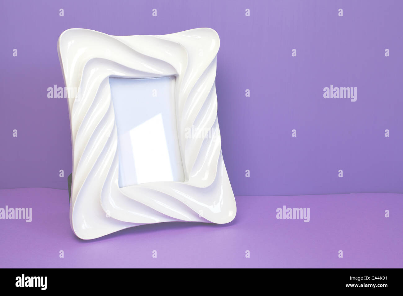 White photo frame on a purple wall. - Stock Image