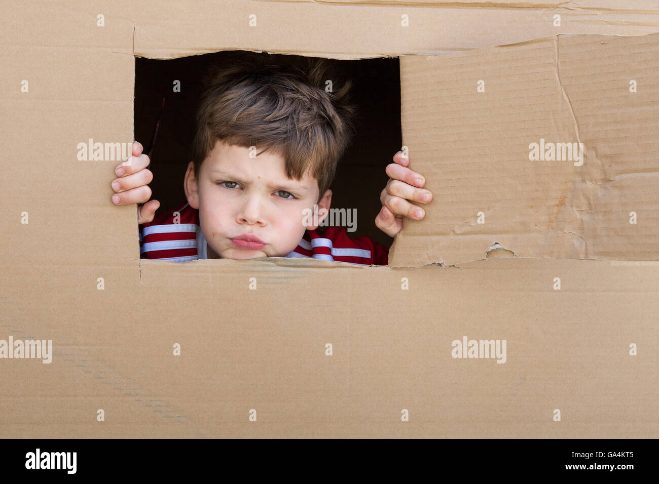 A 7 year old boy looks out of a window cut from a cardboard box - Stock Image