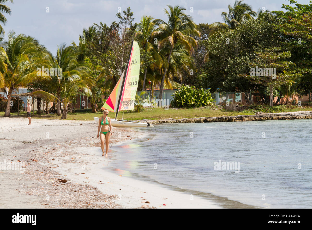 Woman in bikini walking along beach, with Hobie Cat and man in the background, at Playa Larga, Cuba - Stock Image