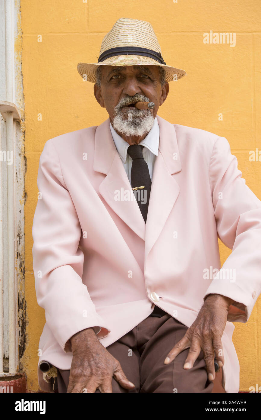 Well-dressed Cuban gentleman in pink blazer with tie sitting outdoors smoking a cigar, Plaza Major, Trinidad, Cuba - Stock Image