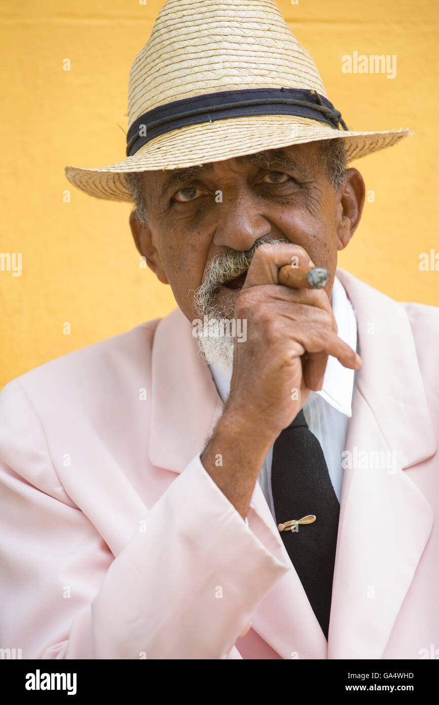Well-dressed Cuban gentleman in pink blazer with tie sitting outdoors smoking a cigar, Plaza Major, Trinidad, Cuba, - Stock Image