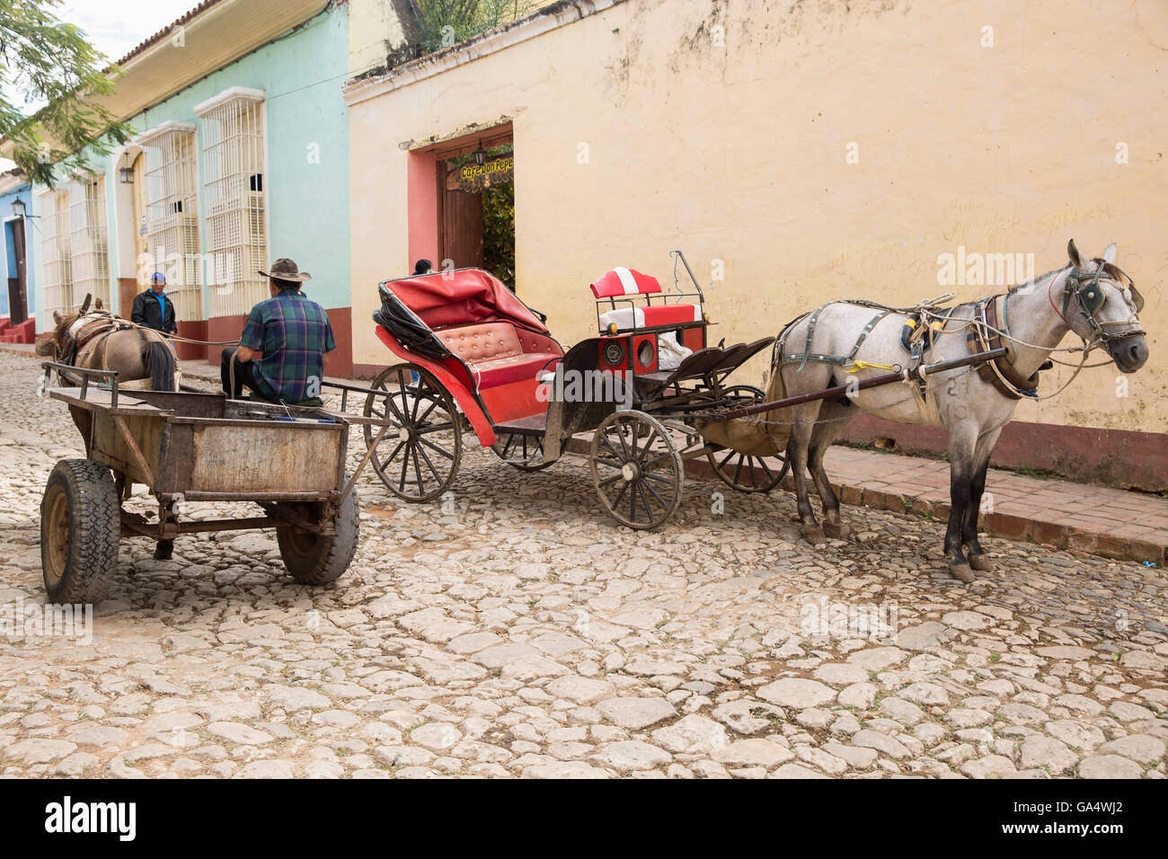 Horse-drawn cart for work and a fancier one for tourists on cobblestone street in Trinidad, Sancti Spiritus, Cuba, - Stock Image