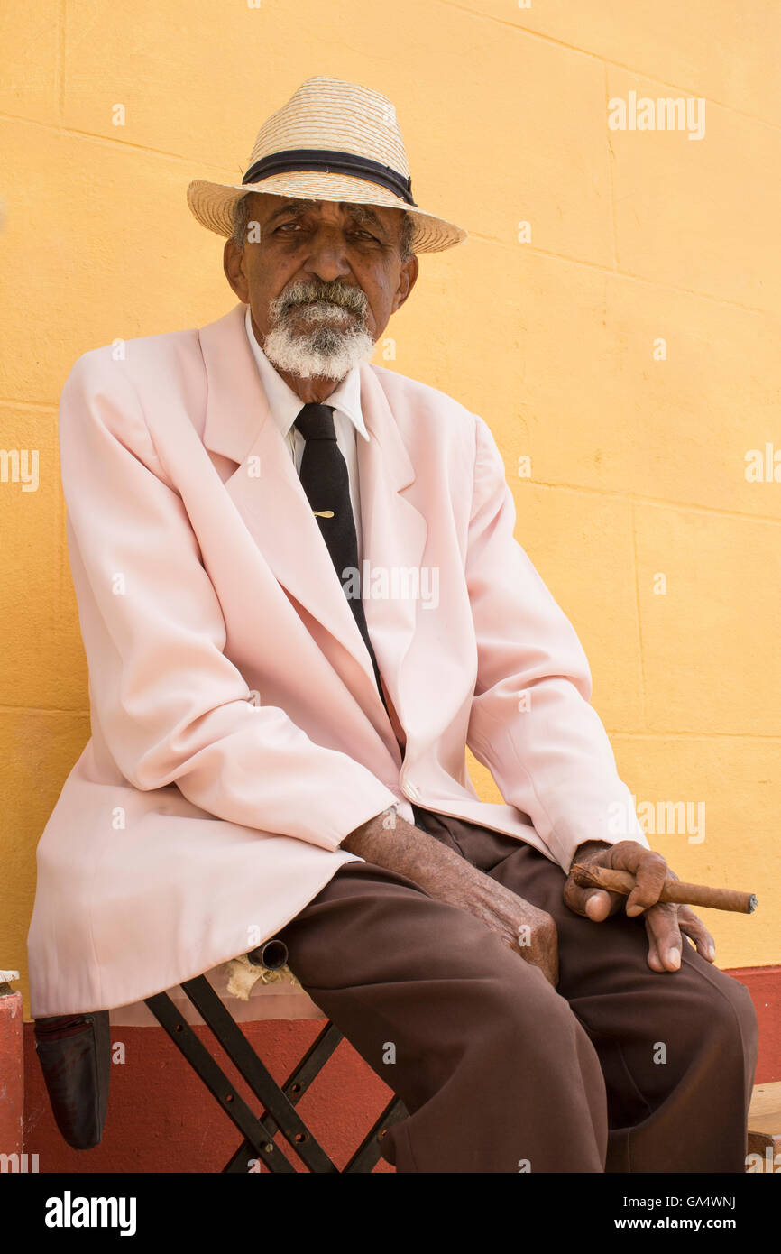 Local man in hat with cigar sitting on stool near Plaza Major, Trinidad, Cuba - Stock Image
