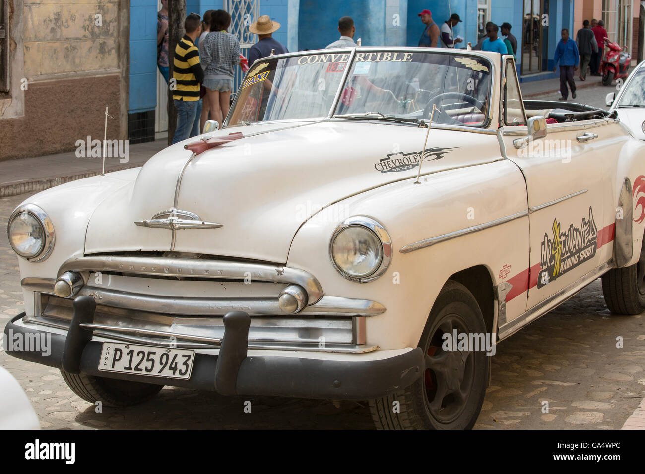 Vintage convertible Chevy taxi parked on a Trinidad street in Cuba, with people in the background - Stock Image