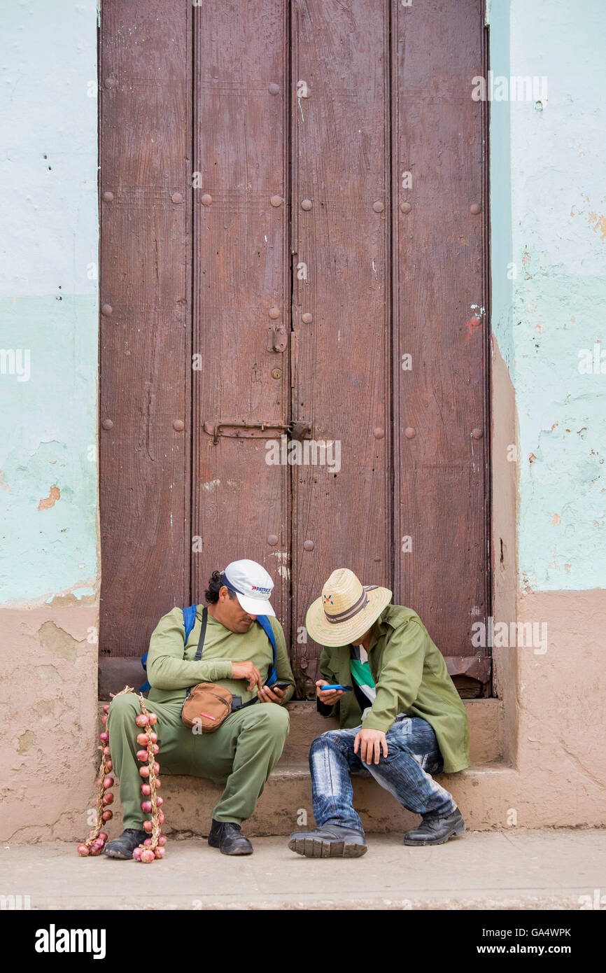 Garlic vendor and friend sit in doorway checking their mobile phones, Trinidad, Sancti Spiritus, Cuba - Stock Image