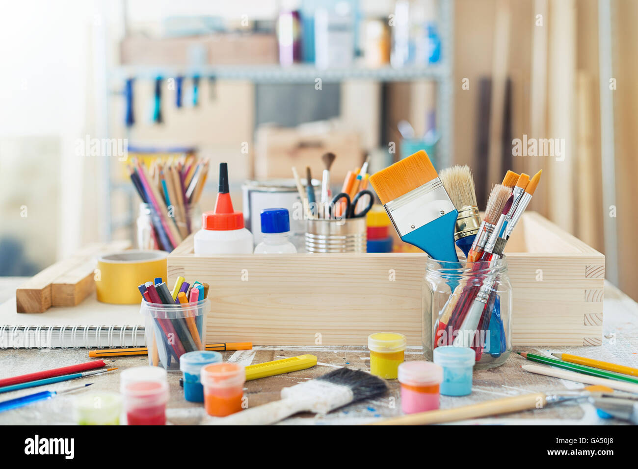 Paint brushes and crafting supplies on the table in a workshop. - Stock Image
