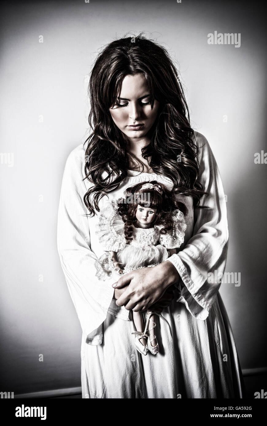 Sad Woman Holding A Vintage Doll