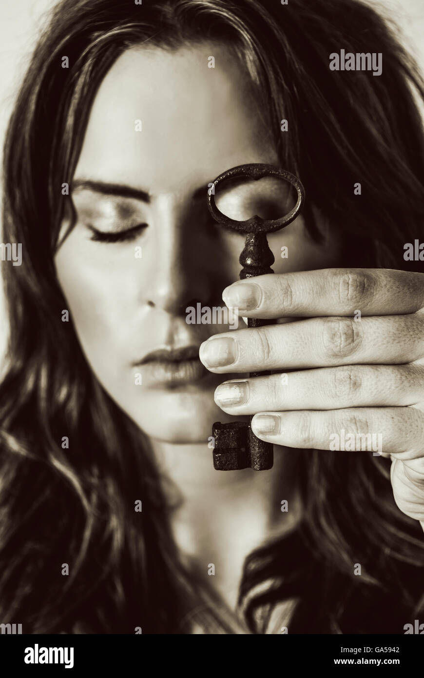 Close up of a sad woman holding a vintage key - Stock Image