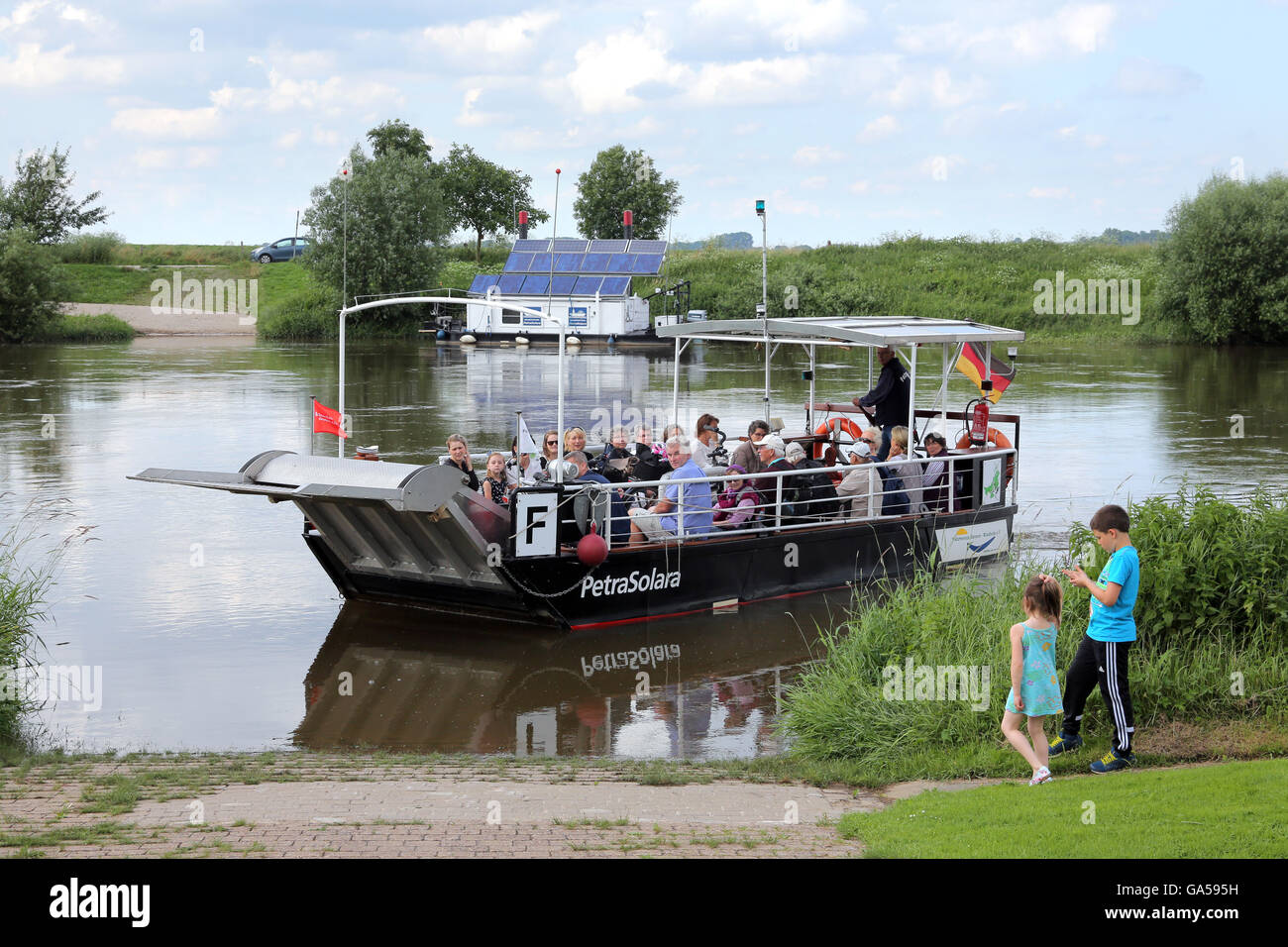 Solar powered ferry PETRA SOLARA across the river Weser near Windheim, Germany. Solar panel station to load batteries - Stock Image