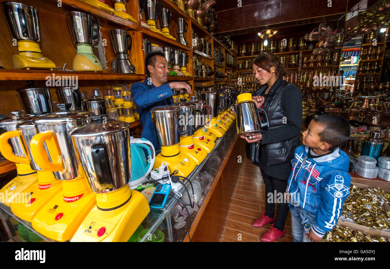 Lhasa. 16th June, 2016. Photo taken on June 16, 2016 shows Purbu (L) talking with customers at his butter barrel - Stock Image