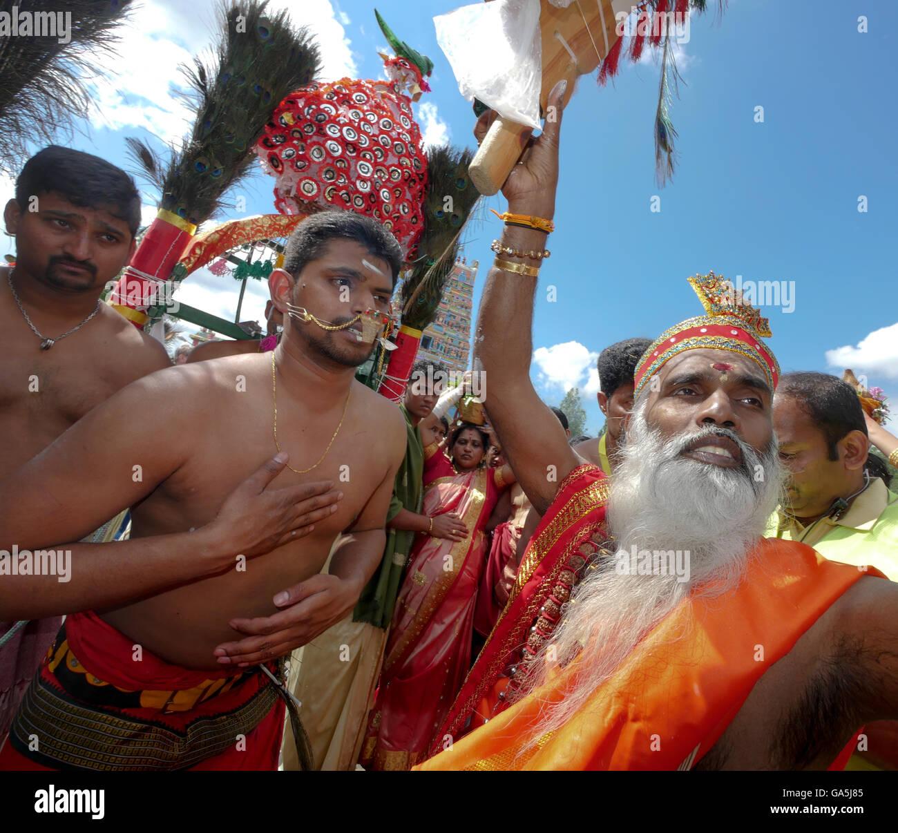 Priest Siva Sri Arumugam Paskarakurukka blesses the Kavadi dancers, Kavadi dancers with by maltreated cheeks during - Stock Image