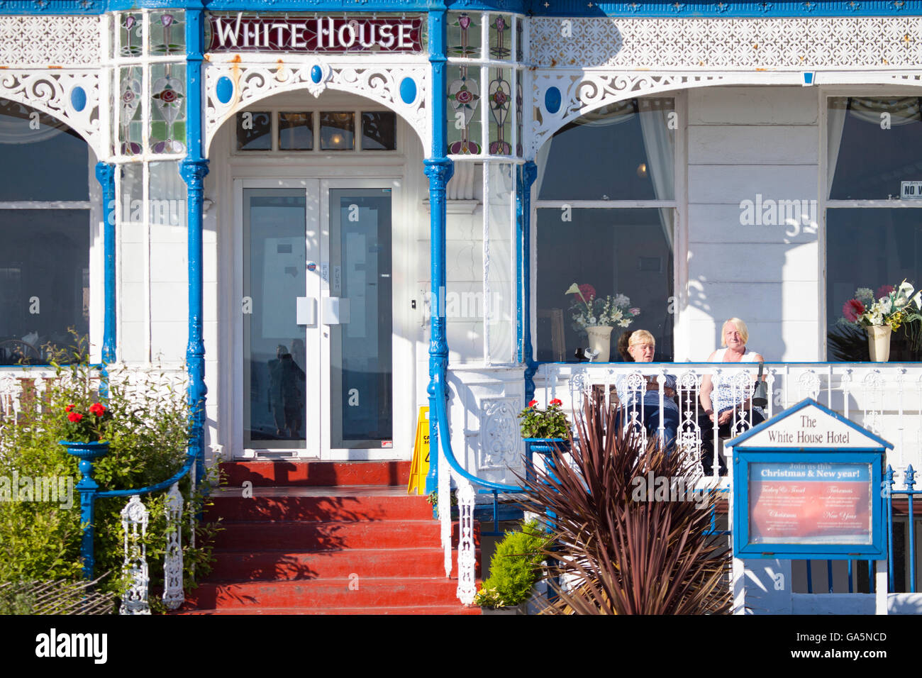 Two woman taking in the morning sunshine sat outside on the veranda of their hotel called the White House at the - Stock Image